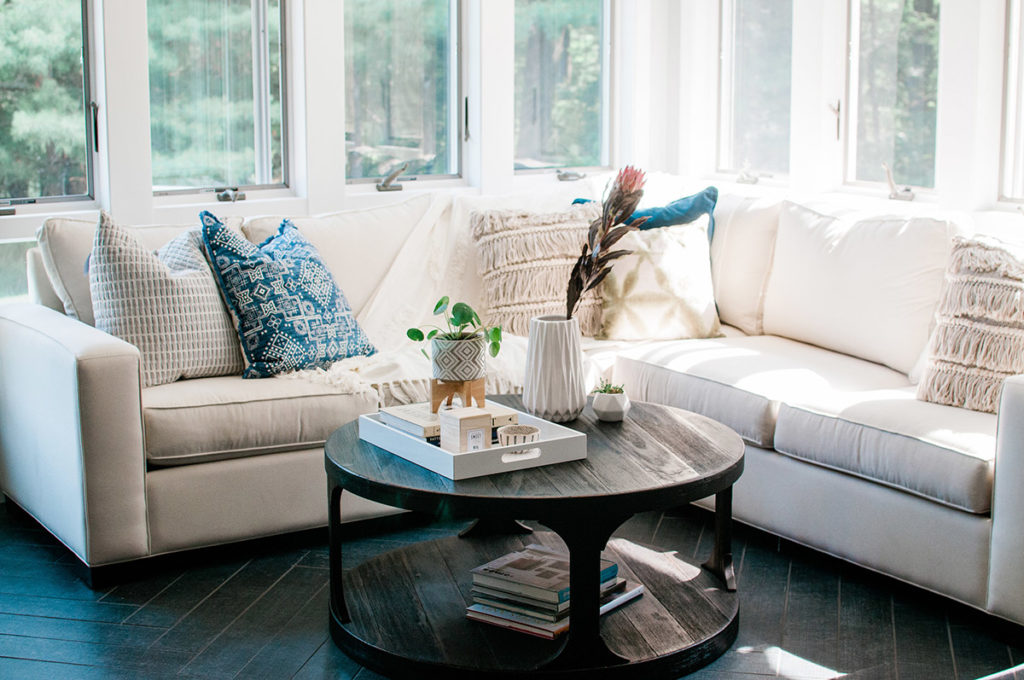 Remodeled living area with wraparound couch and coffee table